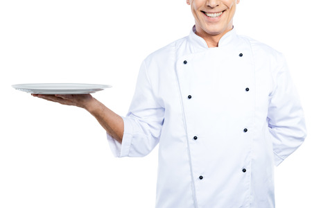 chefs whites: Chef with plate. Close-up of confident mature chef in white uniform holding empty plate and smiling while standing against white background Stock Photo