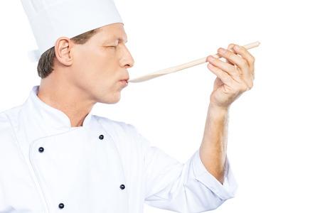 cocinero: Chef tratando comida. Vista lateral de confianza cocinero maduro en blanco uniformes manteniendo los ojos cerrados mientras trataba de comer de cuchara de madera y de pie contra el fondo blanco