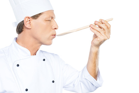 Chef trying meal. Side view of confident mature chef in white uniform keeping eyes closed while trying eating from wooden spoon and standing against white background