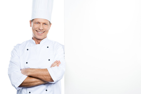 chefs whites: Cheerful chef. Confident mature chef in white uniform leaning at the copy space and smiling while standing against white background