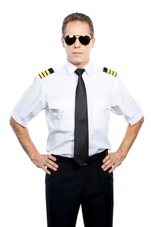 uniform attire: Confident and experienced pilot. Confident male pilot in uniform holding hands on hip while standing against white background Stock Photo