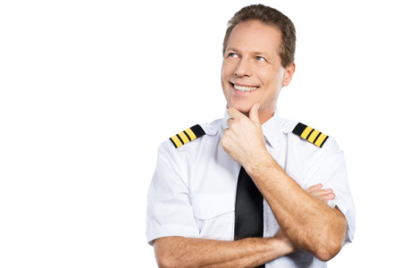 uniform attire: Passionate about sky. Thoughtful male pilot in uniform holding hand on chin and looking up with smile while standing against white background Stock Photo