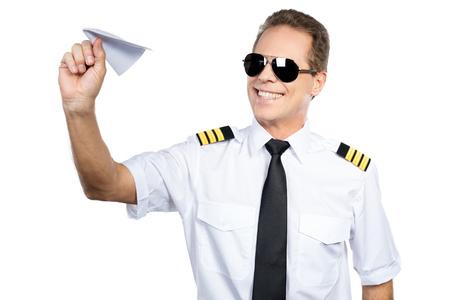 piloto de avion: Apasionada por su trabajo. Piloto de sexo masculino confidente en uniforme jugando con avión de papel mientras está de pie contra el fondo blanco