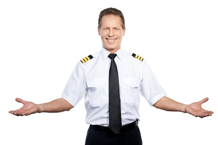 Welcome on board! Happy male pilot in uniform gesturing and smiling while standing against white background 免版税图像