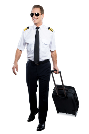 uniform attire: Cheerful pilot. Confident male pilot in uniform walking and carrying suitcase while being isolated on white background