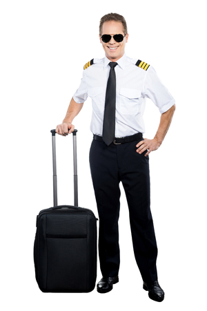 uniform attire: New day and new destination. Confident male pilot in uniform leaning hand on his suitcase and smiling while being isolated on white background Stock Photo