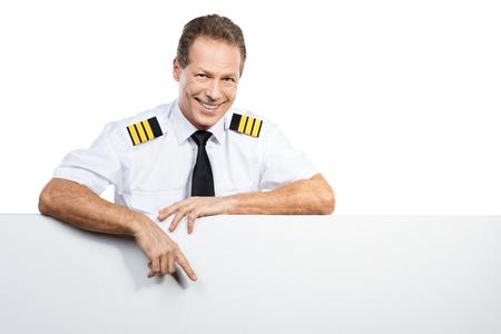 piloto: Basta con mirar a eso. Piloto de sexo masculino confidente en uniforme apoy�ndose en el espacio de la copia y le apunta con una sonrisa mientras est� de pie contra el fondo blanco