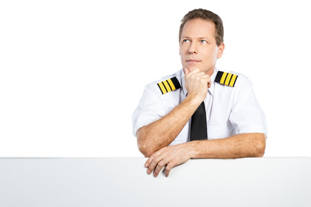 Thoughtful pilot. Thoughtful male pilot in uniform leaning at the copy space and looking away while standing against white background Stock Photo