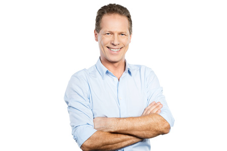 businessman smiling: Confident and successful man. Happy young man in shirt looking at camera and keeping arms crossed while standing against white background