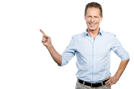 standing against: Pointing copy space. Happy young man in shirt looking at camera and pointing away while standing against white background