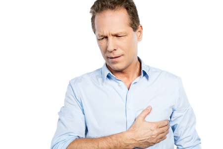 Pain in heart. Frustrated mature man holding hand on heart and expressing negativity while standing against white background