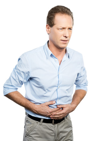 Awful stomachache. Frustrated mature man touching his stomach and expressing negativity while standing against white background Stock Photo