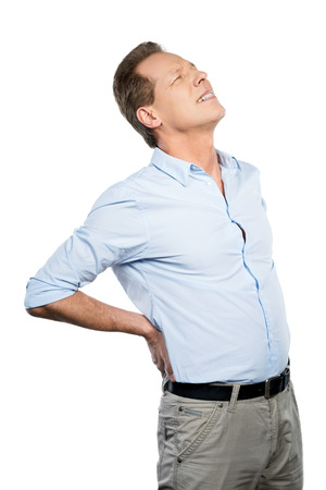 expressing negativity: Feeling pain in back. Frustrated mature man touching his back and expressing negativity while standing against white background