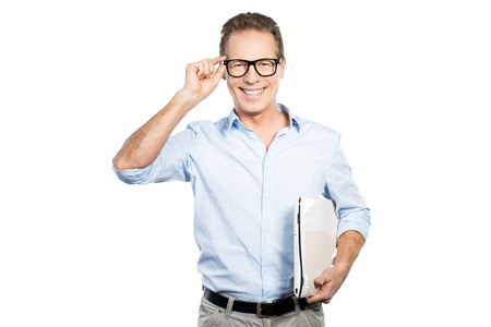 Confident IT expert. Happy mature man in shirt holding laptop and adjusting his eyeglasses while standing against white background