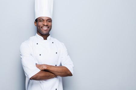 in uniform: La cocina es mi pasi�n. Confiado cocinero africano joven en blancos uniformes manteniendo los brazos cruzados y sonriendo mientras est� de pie contra el fondo gris