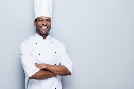 Cooking is my passion. Confident young African chef in white uniform keeping arms crossed and smiling while standing against grey background