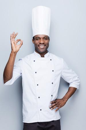 cocinero: El chef, confiable. Confiado cocinero africano joven en uniforme blanco gesticular signo de OK y sonriendo mientras est� de pie contra el fondo gris Foto de archivo