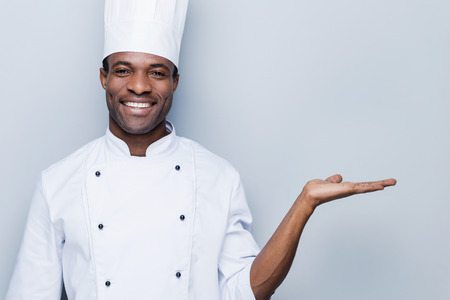 chefs whites: Cheerful chef. Confident young African chef in white uniform holding copy space and smiling while standing against grey background