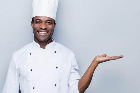 cocinero: Cocinero alegre. Confiado cocinero africano joven en uniforme blanco celebraci�n copia espacio y sonriente mientras est� de pie contra el fondo gris