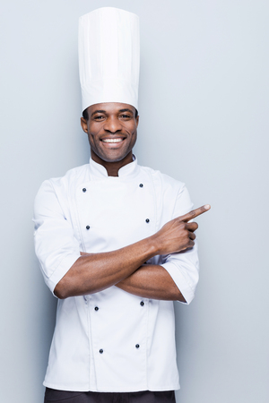 black professional: Special offer from chef. Confident young African chef in white uniform pointing away and smiling while standing against grey background Stock Photo