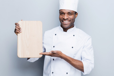 chefs whites: Special offer from chef. Confident young African chef in white uniform holding wooden cutting board and pointing it with smile while standing against grey background