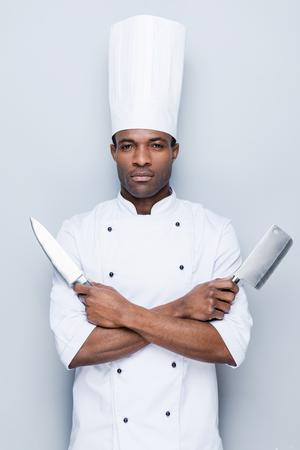 cocinero: Listo para trabajar. Confiado cocinero africano joven en uniforme blanco sosteniendo cuchillos en sus manos y mirando a la c�mara mientras est� de pie contra el fondo gris