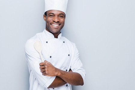 chef uniform: Confident chef. Cheerful young African chef in white uniform keeping arms crossed and smiling while standing against grey background