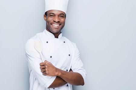 chef cocinando: El chef, confiable. Alegre cocinero africano joven en blancos uniformes manteniendo los brazos cruzados y sonriendo mientras est� de pie contra el fondo gris