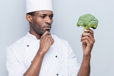chefs whites: Choosing the best ingredient for his meal. Thoughtful young African chef in white uniform holding broccoli and looking at it while standing against grey background Stock Photo