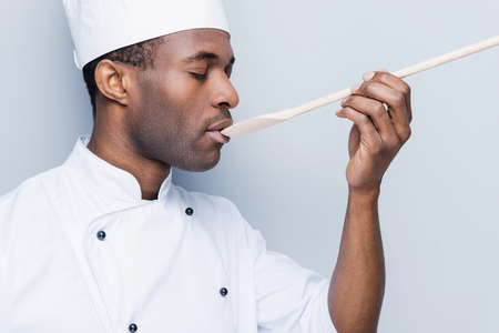 chefs whites: Chef trying meal. Side view of confident young African chef in white uniform keeping eyes closed while trying eating from wooden spoon and standing against grey background