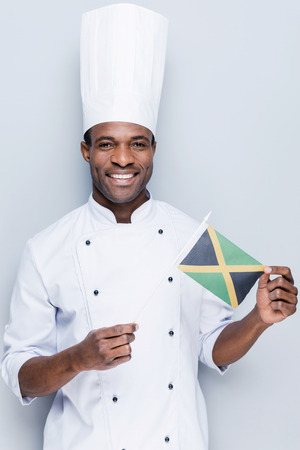 chefs whites: Loving to cook national food. Confident young African chef in white uniform holding flag of Jamaica and smiling while standing against grey background