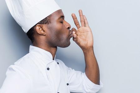 chef cocinando: Esta comida es simplemente perfecto! Vista lateral de confianza cocinero africano joven en blancos uniformes manteniendo los ojos cerrados y gesticulando mientras est� de pie contra el fondo gris