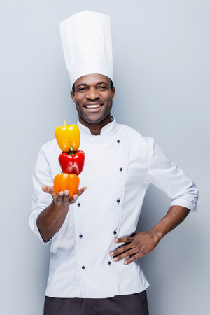 chefs whites: Colorful culinary. Confident young African chef in white uniform holding multi colored peppers and looking at camera with smile while standing against grey background