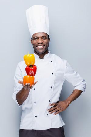 cocinero: Culinaria colorido. Confiado cocinero africano joven en uniforme blanco que sostiene m�ltiples pimientos de colores y mirando a c�mara con una sonrisa, mientras que de pie sobre fondo gris Foto de archivo
