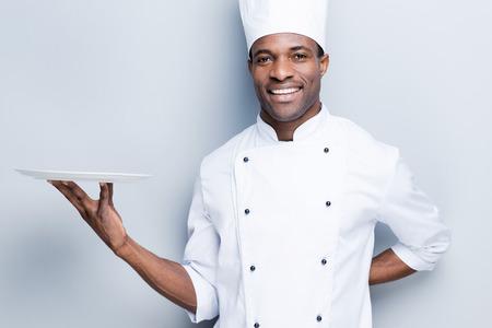 Copie el espacio en su plato. Confiado cocinero africano joven en uniforme blanco que sostiene el plato vacío y sonriendo mientras está de pie contra el fondo gris