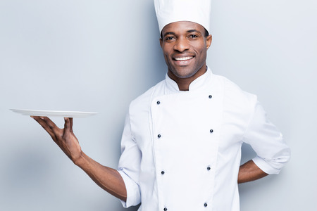 african background: Copy space at his plate. Confident young African chef in white uniform holding empty plate and smiling while standing against grey background