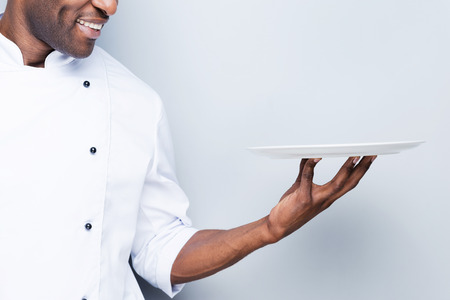 chefs whites: Chef with plate. Close-up of confident young African chef in white uniform holding empty plate and smiling while standing against grey background Stock Photo