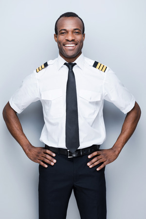 hand on hip: Confident pilot. Confident African pilot in uniform holding hand on hip and smiling while standing against grey background