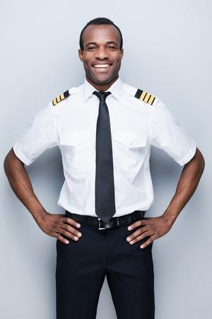 �uniform: Piloto confiado. Piloto africano Confiados en uniforme con la mano en la cadera y sonriendo mientras est� de pie contra el fondo gris Foto de archivo