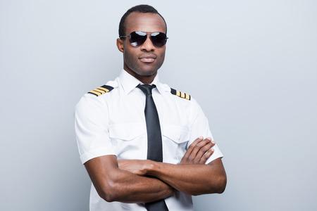 自信を持って、経験豊富なパイロット。灰色の背景に対して立っている制服維持、腕組みで自信を持ってアフリカ パイロット