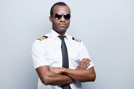 piloto: Confiado y piloto experimentado. Piloto africano Confiados en brazos uniformes manteniendo cruzó mientras está de pie contra el fondo gris