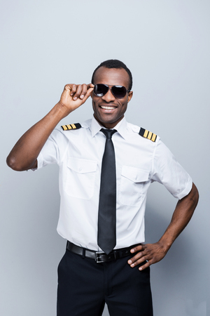 pilot: Confident pilot. Confident African pilot in uniform adjusting his eyeglasses and smiling while standing against grey background
