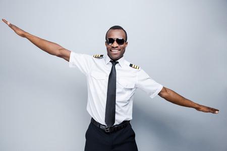 piloto: Como un avi�n. Piloto africana feliz en uniforme gesticulando y sonriendo mientras est� de pie contra el fondo gris Foto de archivo