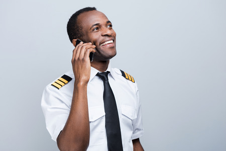 uniform attire: Sharing news after landing. Side view of happy African pilot in uniform holding mobile phone and looking away while standing against grey background Stock Photo