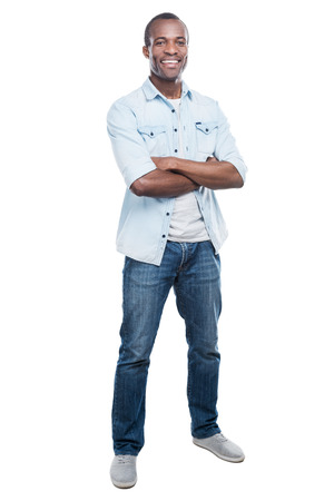 casually: Casually handsome. Full length of handsome young black man keeping arms crossed and smiling at camera while standing against white background