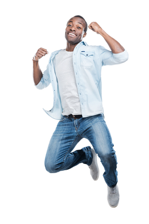 excitación: Lo hice! Longitud total de hombre negro joven y guapo saltando sobre fondo blanco