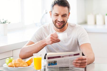 colazione: Partendo giorno da una buona notizia. Bel giovane leggendo il giornale e sorridente mentre beve il caffè e con l'uomo prima colazione in cucina