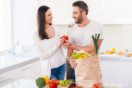 Living a healthy life together. Beautiful young couple unpacking shopping bag full of fresh vegetables and smiling while standing in the kitchen together