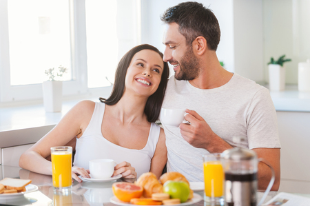 romance: Enjoying Sunday morning together. Beautiful young couple bonding to each other and smiling while sitting in the kitchen together and having breakfast