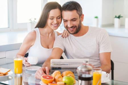 desayuno romantico: Buenos días comienza a partir de una buena noticia. Hermosa joven pareja de unión entre sí y la lectura de periódicos junto sentado en la cocina y desayunar